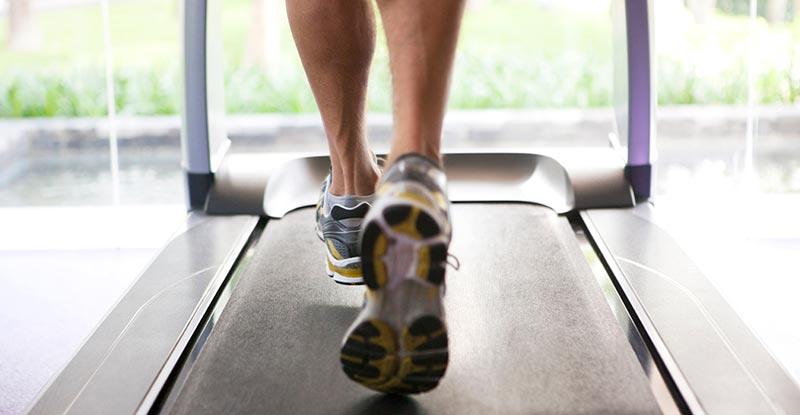 پاهای یک آقا در حال دویدن روی تردمیل