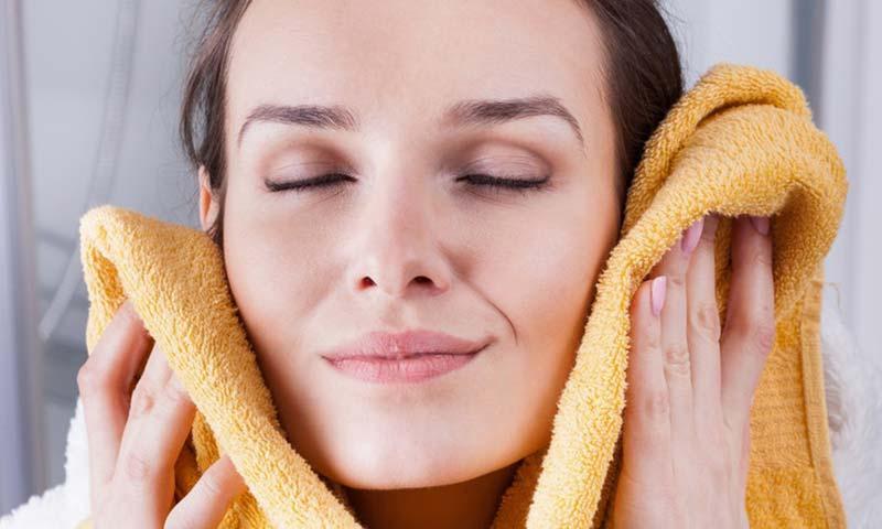 یک خانم در حال خشک کردن صورت با حوله