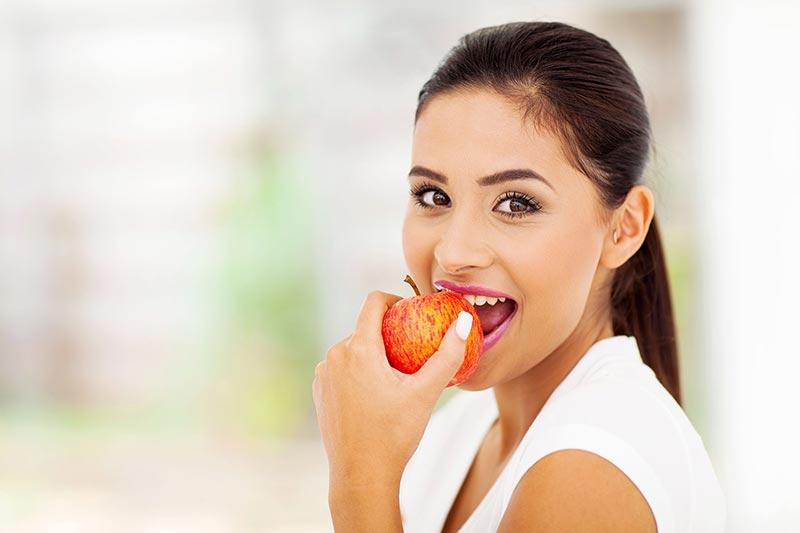 یک خانم در حال سیب خوردن برای لاغری سریع