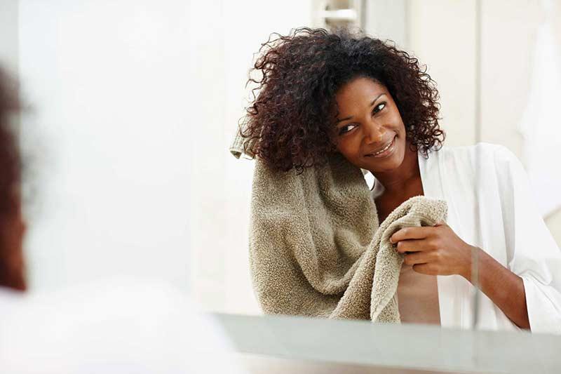 یک خانم سیاه پوست در حال خشک کردن موهای فر خود