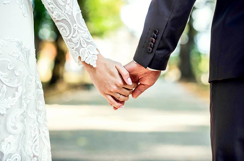یک عروس و داماد که دست های هم را گرفته اند