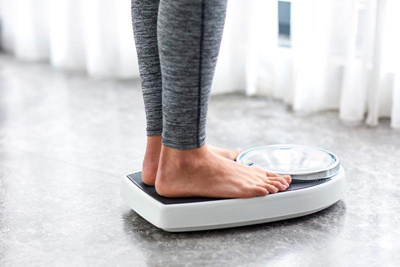 یک خانم در حال وزن کردن خود با ترازو