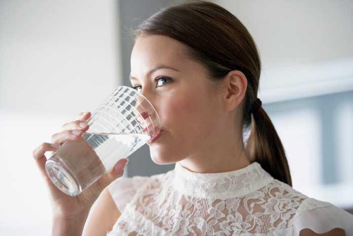 یک خانم در حال نوشیدن آب با غذا