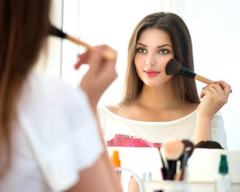 یک خانم در حال انجام آرایش صورت