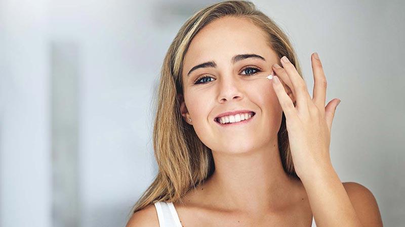 یک خانم در حال استفاده از کرم روی صورت خود