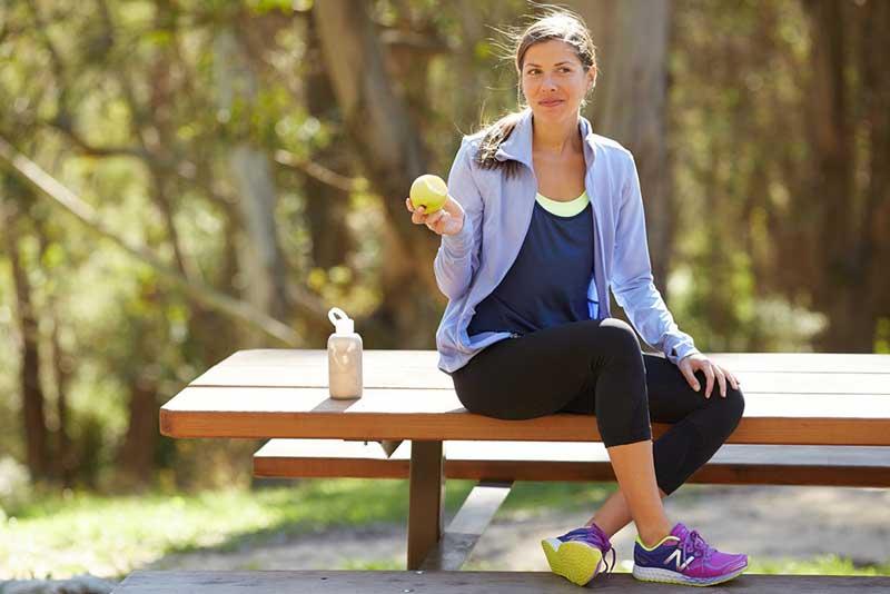 یک خانم ورزشکار در حال خوردن سیب