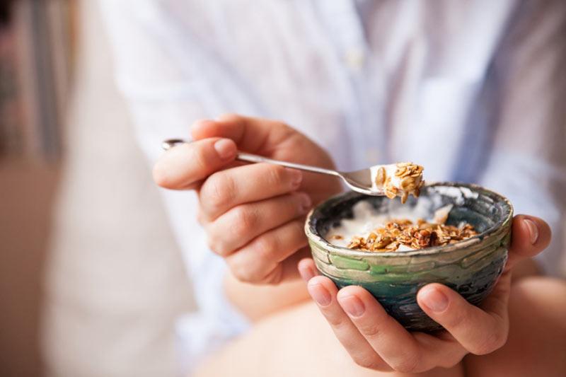 یک خانم در حال خوردن صبحانه