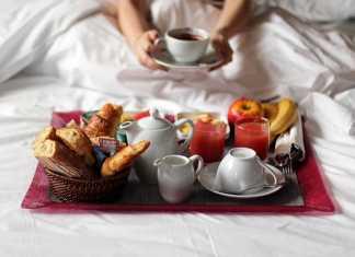 یک خانم در حال خوردن صبحانه برای لاغری و کاهش وزن در تخت خواب