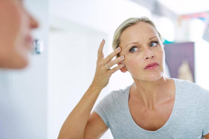 یک خانم در حال بررسی کردن لاغری صورت خود