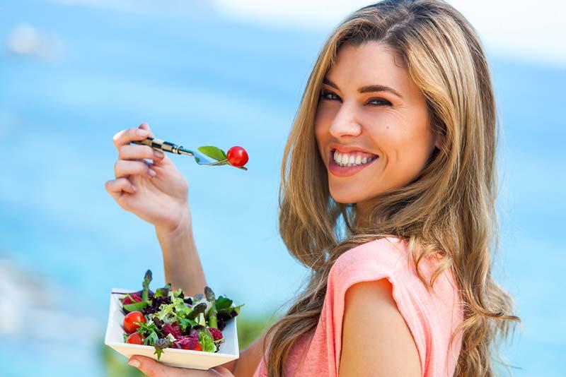 یک خانم در حال خوردن سالاد به عنوان یک غذای رژیمی سالم