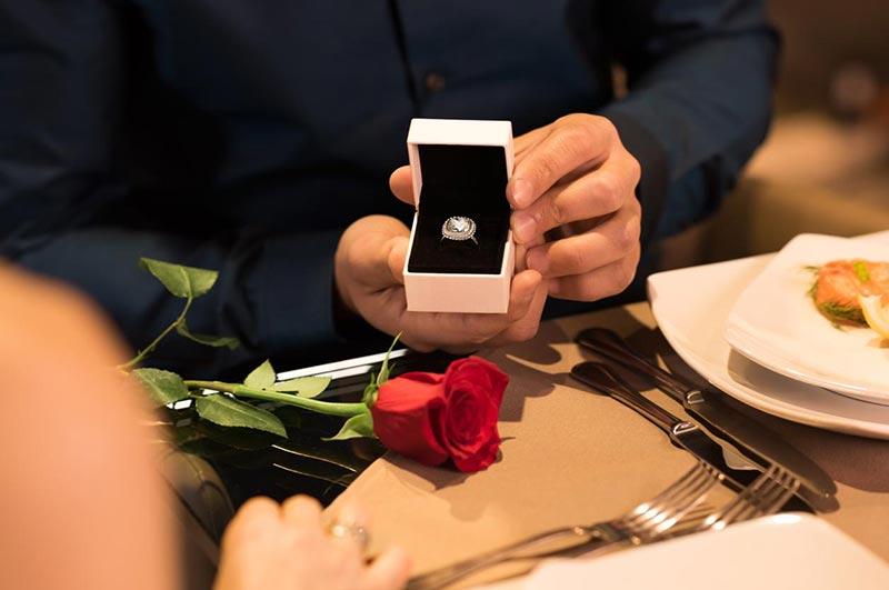 یک آقا در حال خواستگاری کردن در رستوران با گل رز و حلقه