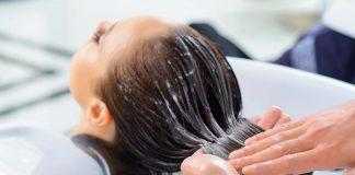 یک خانم در حال کراتینه کردن مو در آرایشگاه