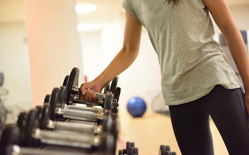 برداشتن دمبل برای انجام تمرینات وزنه ای