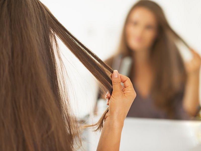 یک خانم در حال دست کشیدن به موهای صاف و کراتینه شده خود