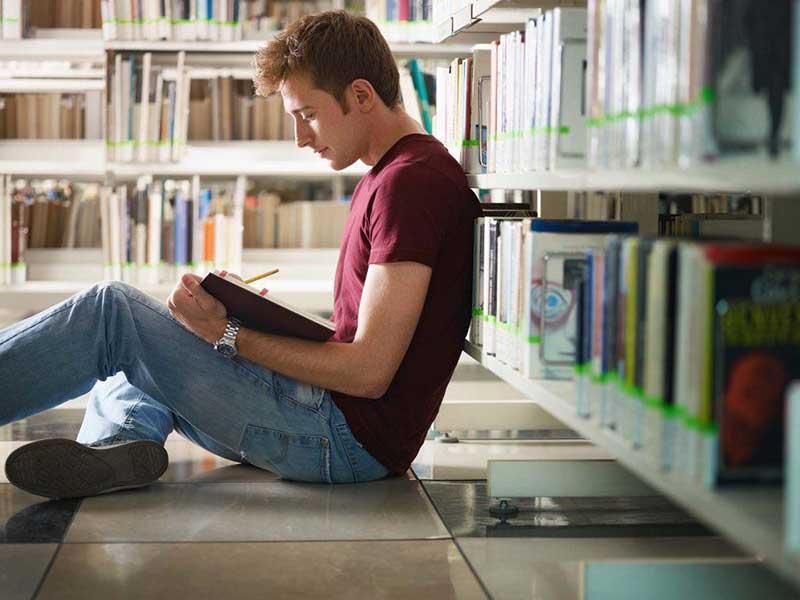 پسری در حال خواندن کتاب در کتابخانه دانشگاه