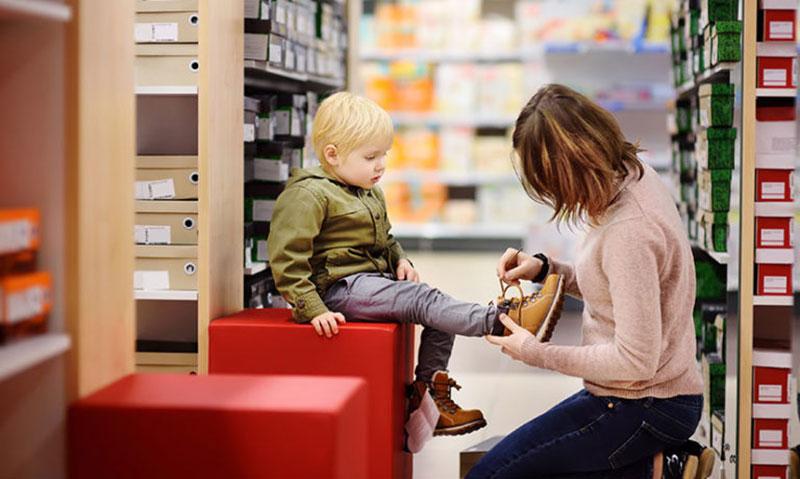 مادر در حال خرید کفش مناسب برای فرزند خود