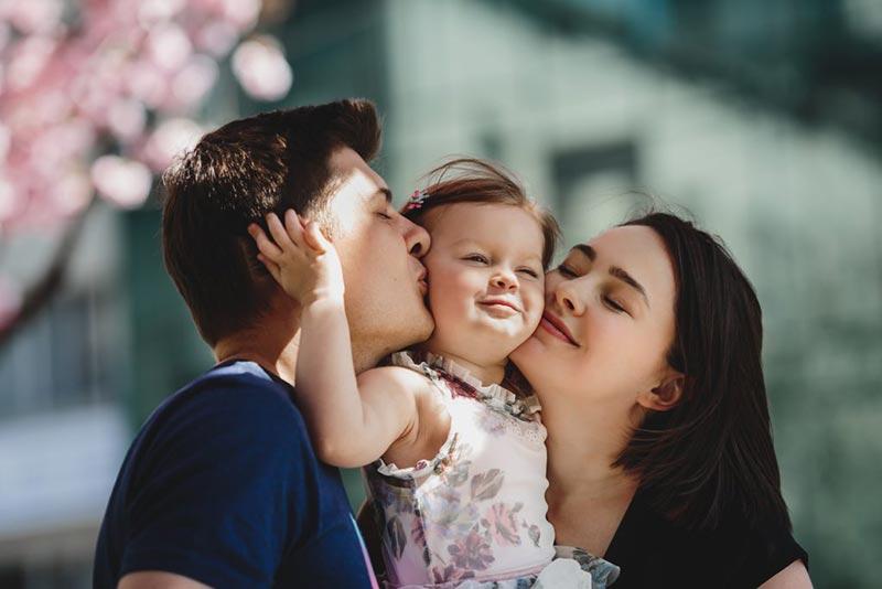 پدر و مادر در حال بوسیدن فرزند خود