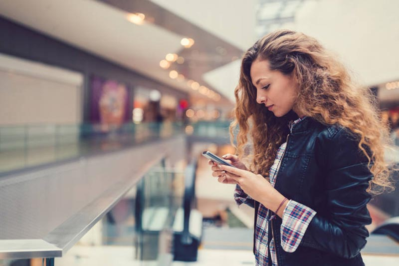 یک خانم با موهای فر در حال پیام دادن