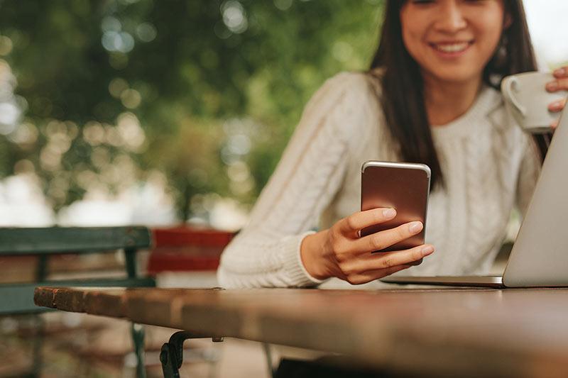 یک خانم در حال پیام دادن با تلفن همراه