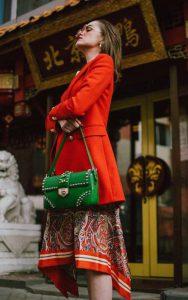 پالتوی قرمز و دامن طرحدار با کیف سبز