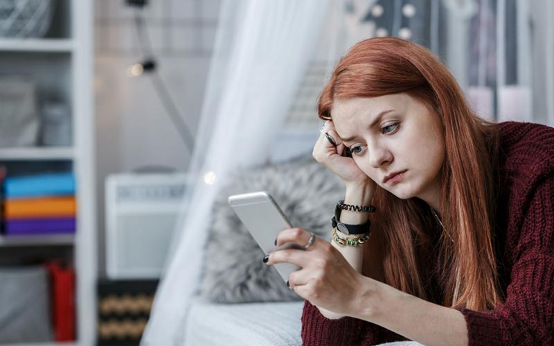 یک خانم ناراحت در حال پیام دادن