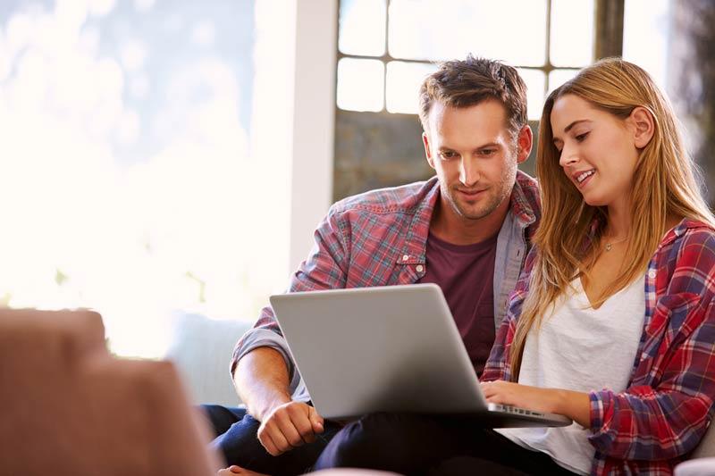زن و شوهر در حال بررسی موضوعی در لپ تاپ