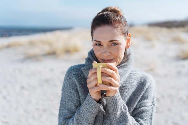 یک خانم در حال خوردن چای یا دمنوش