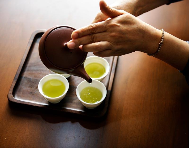 ریختن چای سبز از قوری به فنجان