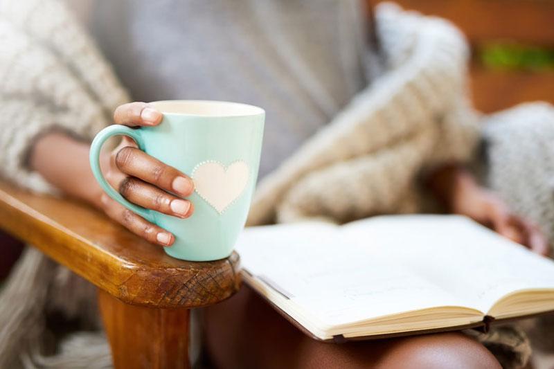 یک خانم در حال خواندن کتاب و نوشیدن چای یا دمنوش