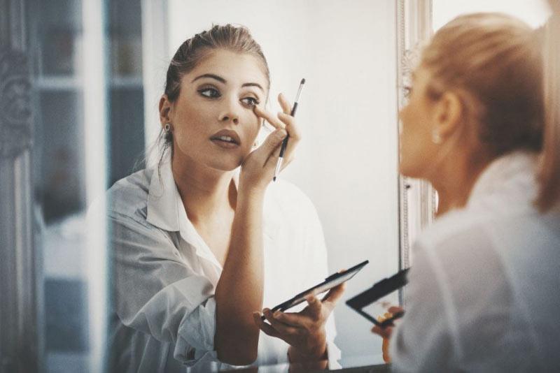 یک خانم در حال انجام آرایش جشم