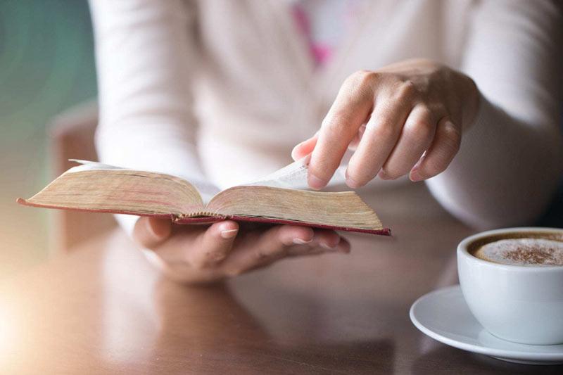 یک خانم در حال خواندن کتاب و خوردن قهوه