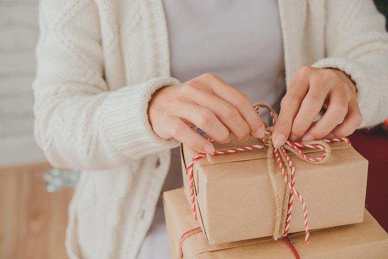 یک خانم در حال باز کردن چند جعبه کادوی ساده