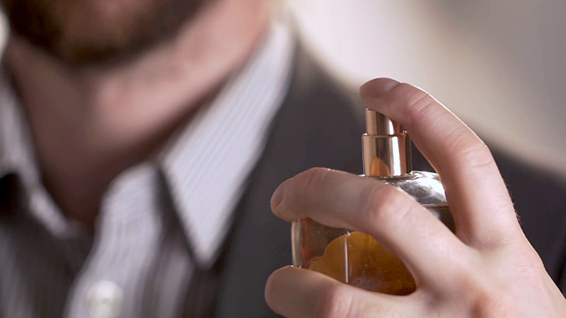 یک آقا در حال استفاده از عطر